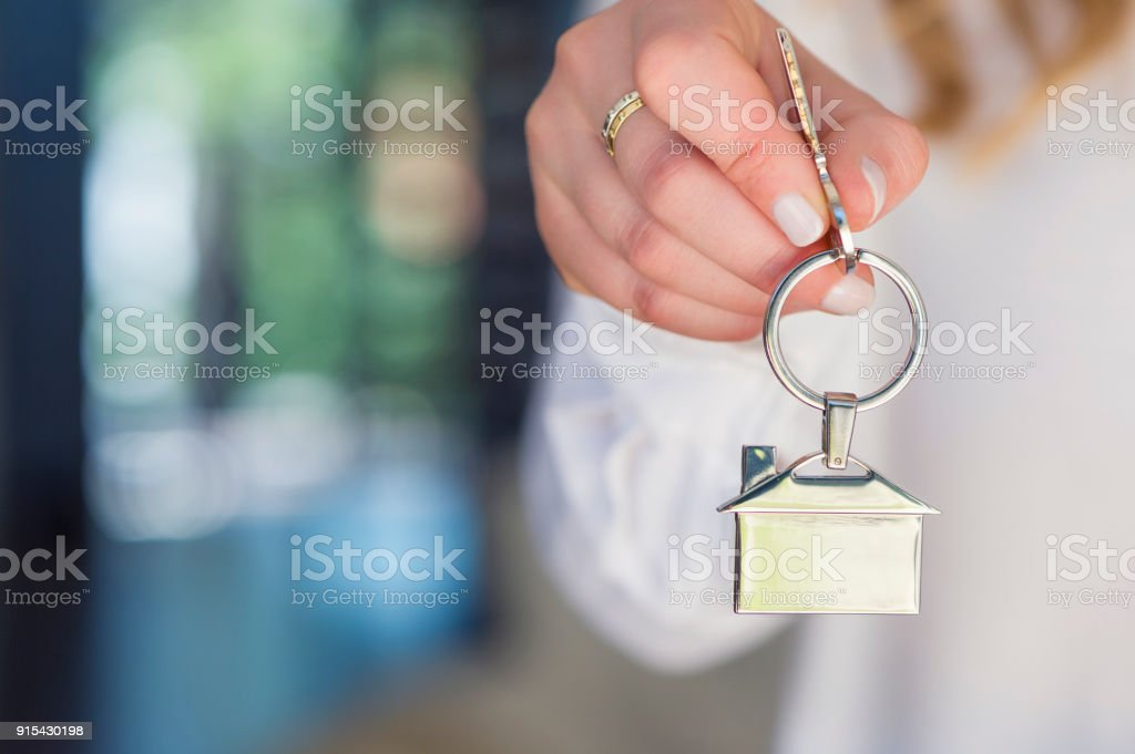 Business Woman offering a house key. stock photo