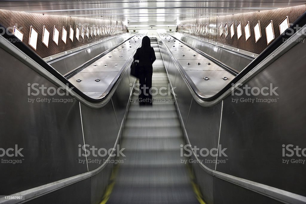 Mujer de negocios en un moderno escalera mecánica foto de stock libre de derechos