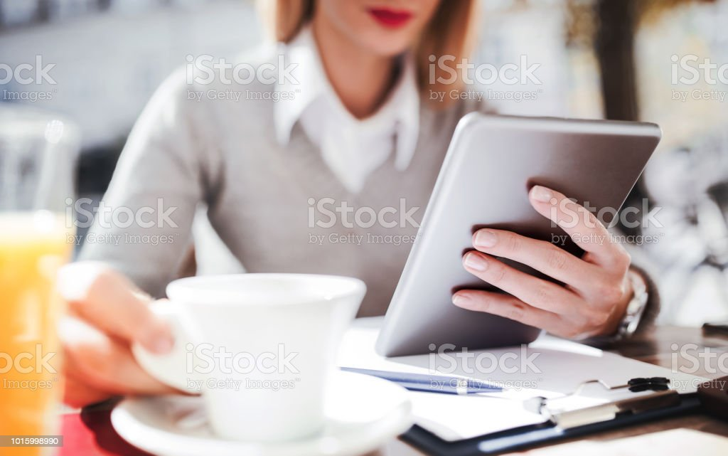Young businesswoman sitting in a cafe drinking coffee and using...