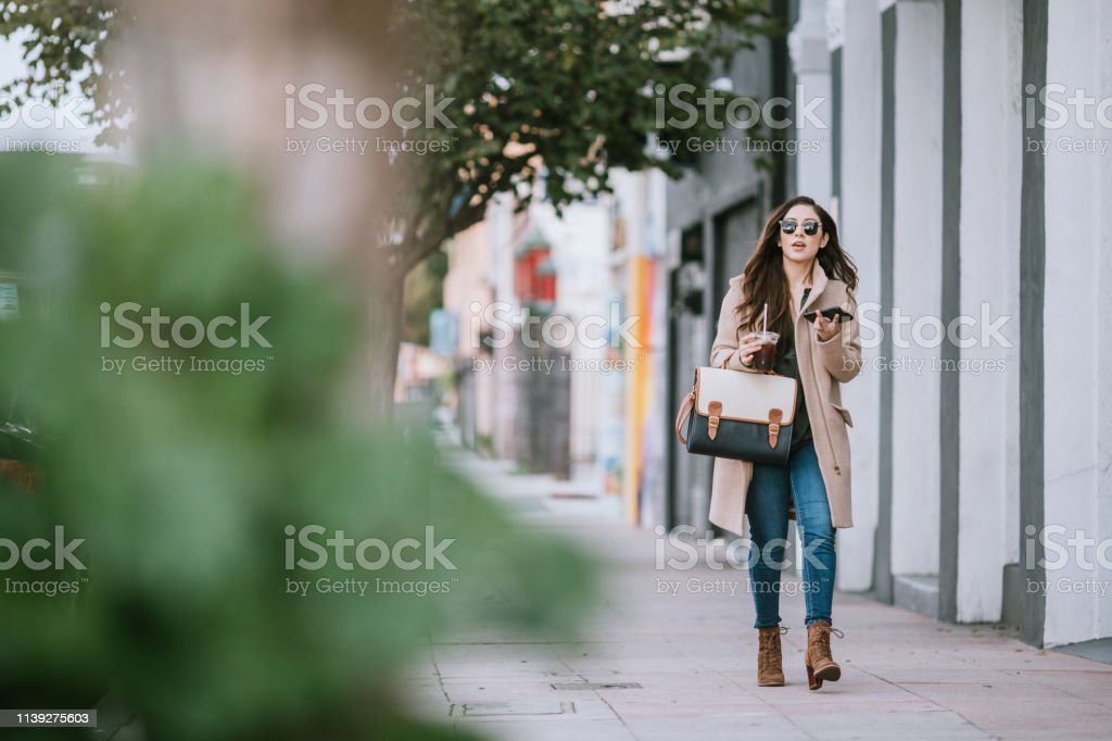 A Latina woman takes a business call as she walks from her car to her...