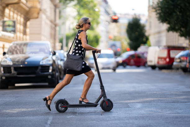 business woman on the move commuting to work with electric push scooter stock photo