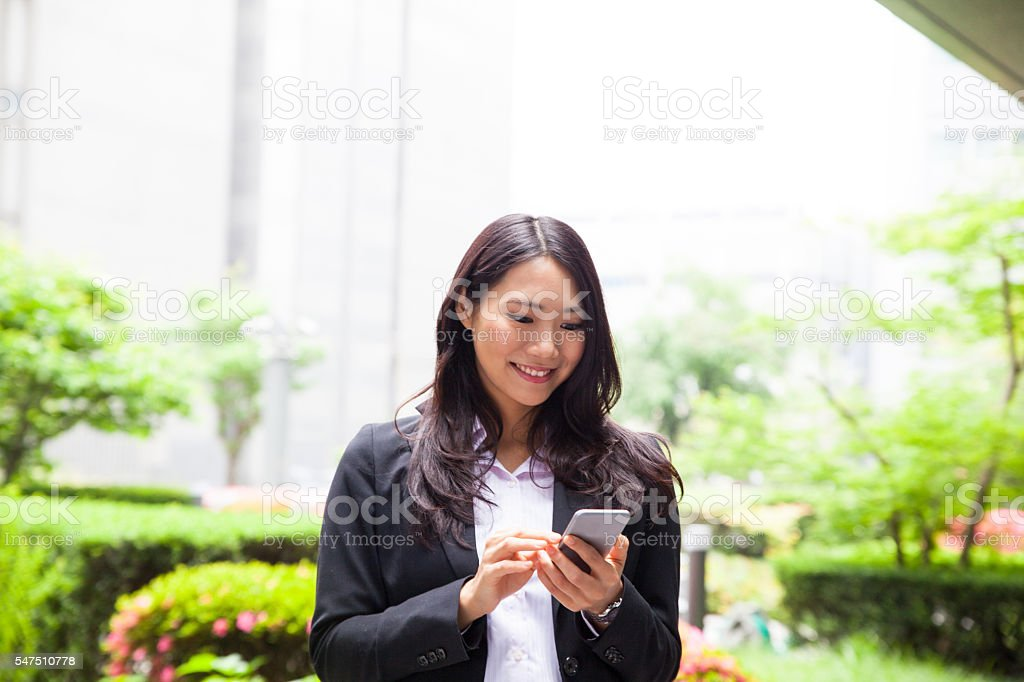 Business woman outdoors working on her mobile phone stock photo