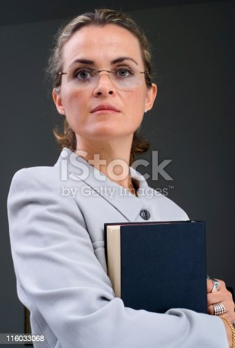 caucasian business woman looking at the camera holding a book