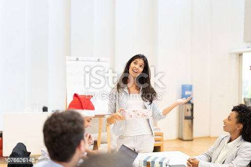 istock Business woman playing a game Exchanging Christmas presents at work / Amigo Secreto 1076626148