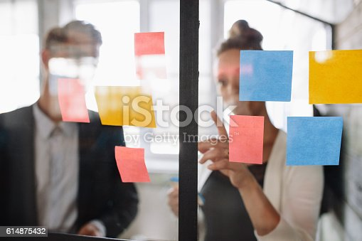 496441730 istock photo Business woman pointing at sticky note to male colleague 614875432