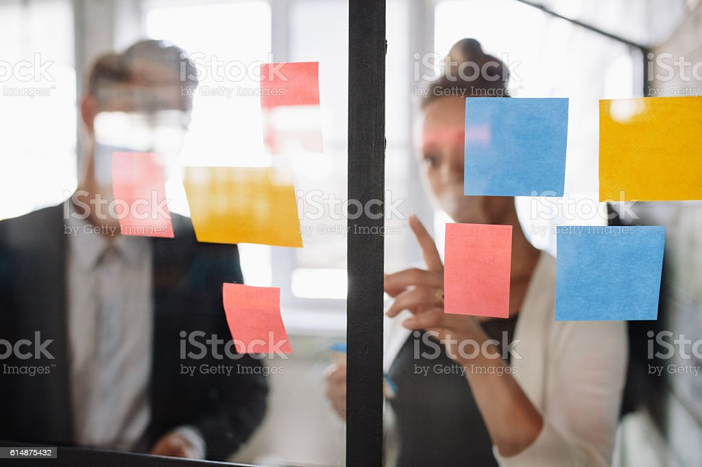 Business woman pointing at sticky note to male colleague stock photo