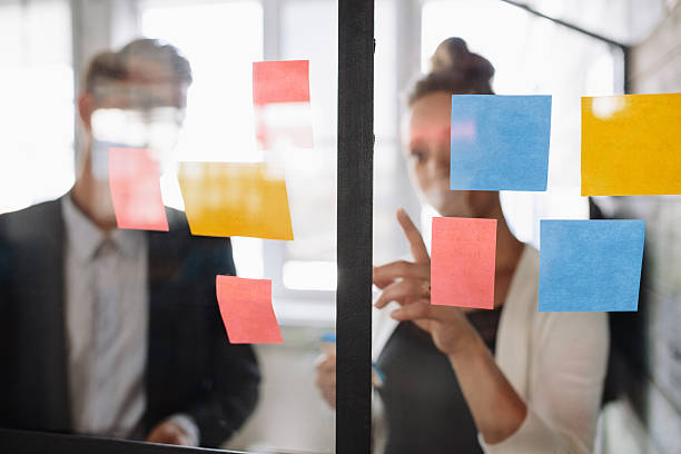 Business woman pointing at sticky note to male colleague - foto de acervo