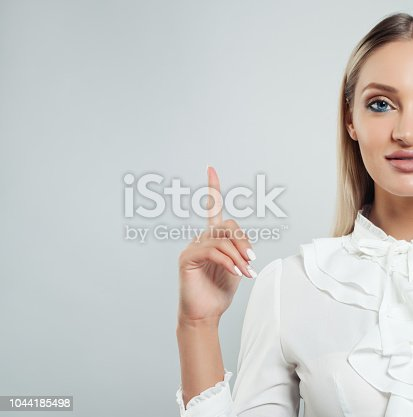 Business woman pointing her finger up on white background with copy space