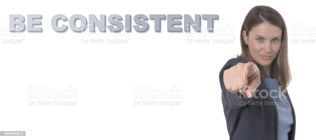 Business Woman pointing the text BE CONSISTENT Business Concept. stock photo