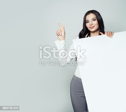 Business woman portrait. Businesswoman pointing to empty grey background and holding white banner background. Seo and advertising marketing concept