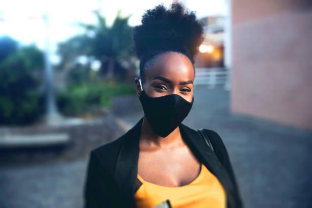 Business woman portrait wearing a black face mask stock photo