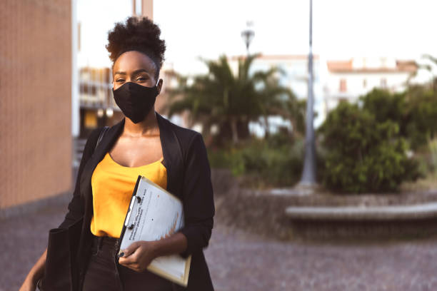 Business woman portrait wearing a black face mask stock photo