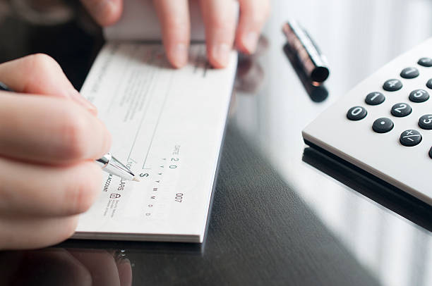 business woman prepare writing a check - blank check stock photos and pictures
