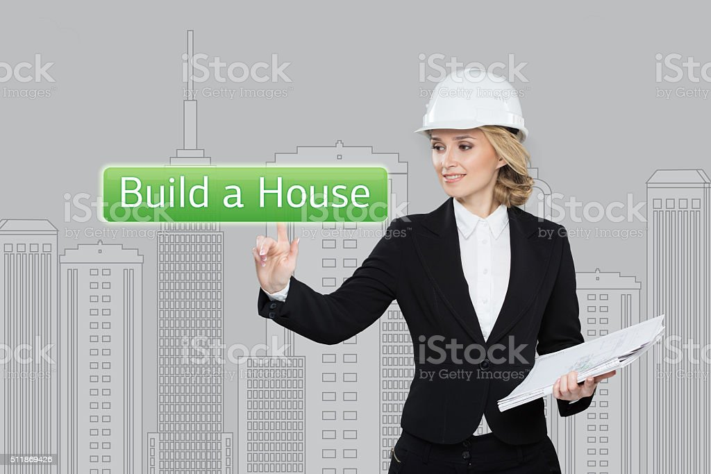 Business woman pressing build a hause button on virtual screens stock photo