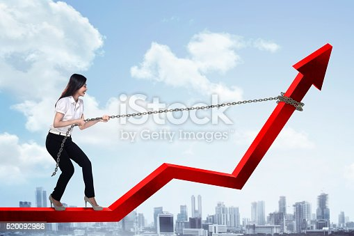 istock Business Woman Pulling Arrow With Chain 520092986