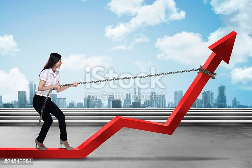istock Business Woman Pulling Arrow With Chain 524542284