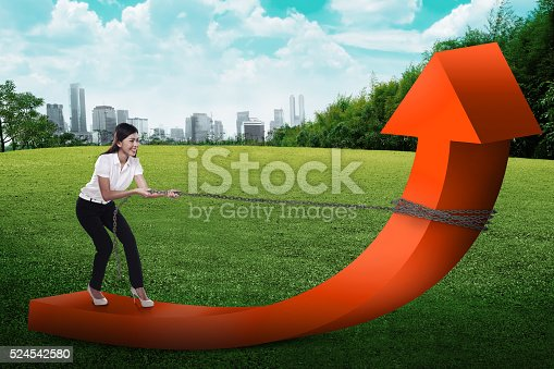 istock Business woman pulling arrow with chain 524542580