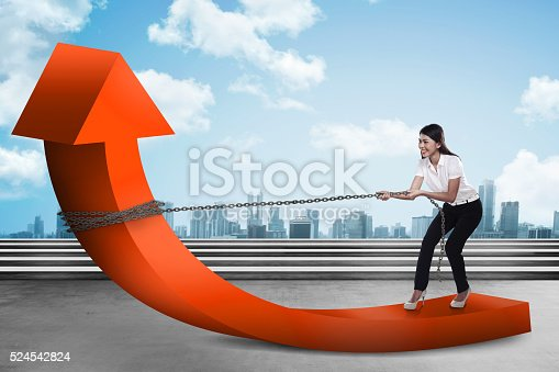 istock Business woman pulling arrow with chain 524542824