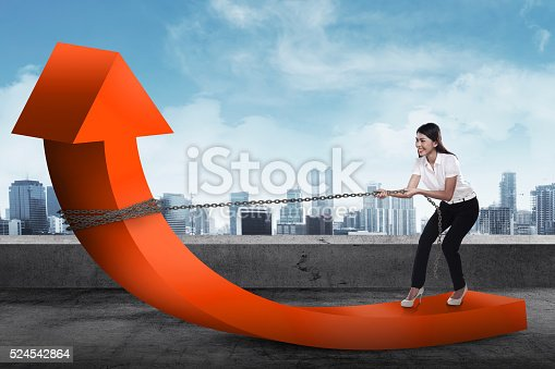 istock Business woman pulling arrow with chain 524542864