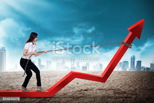 istock Business Woman Pulling Arrow With Chain 524543476