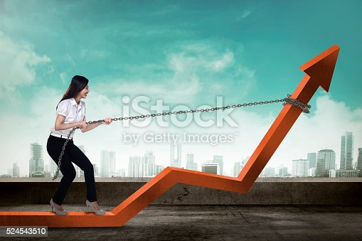 istock Business Woman Pulling Arrow With Chain 524543510
