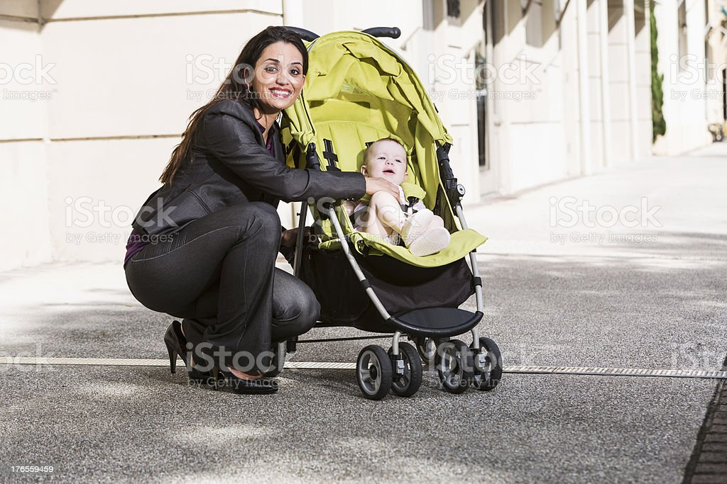 Business woman pushing baby stroller stock photo