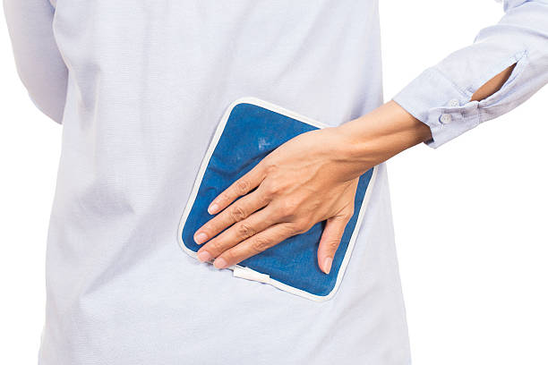 business woman putting an ice pack on her back pain - crioterapia foto e immagini stock
