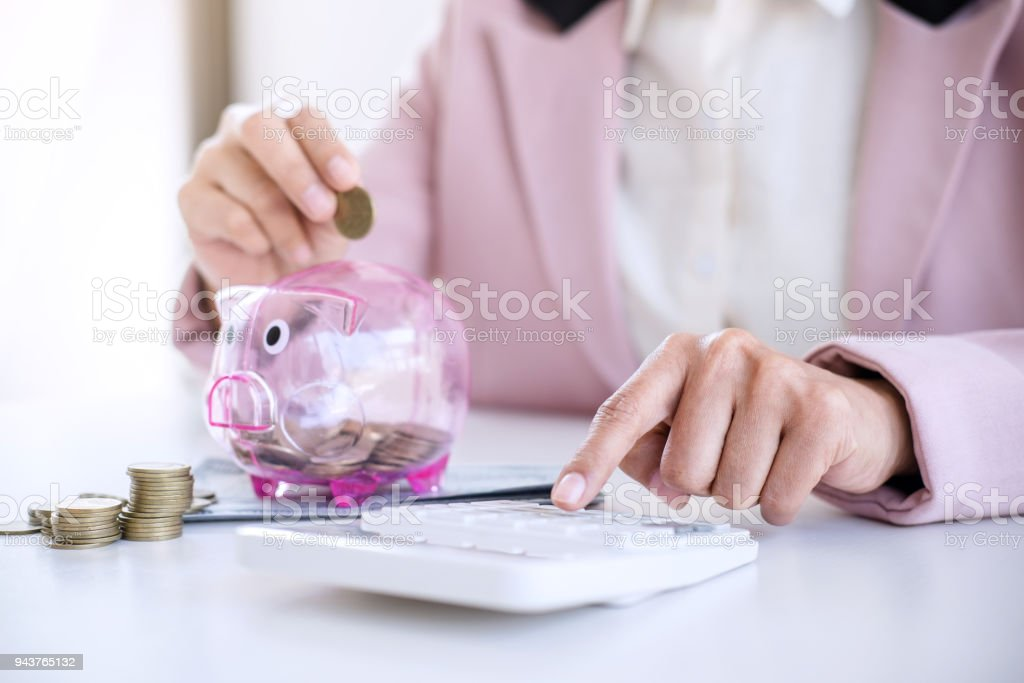 Business woman putting coins into piggy bank and using calculator to analysis business investment strategy with income of money coin and dollar, financial concept stock photo