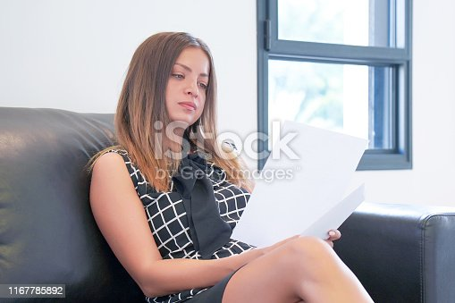 istock business woman reading a document in office workspace. 1167785892