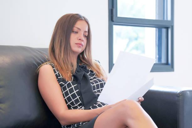Geschäftsfrau, die ein Dokument im Büroarbeitsbereich liest. – Foto