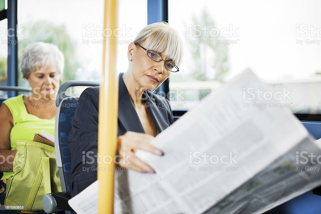 Business woman reading newspapers in bus. royalty-free stock photo