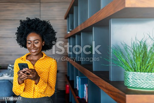 Quick message to friend. Attractive young African woman holding smart phone and looking at it while standing indoors.