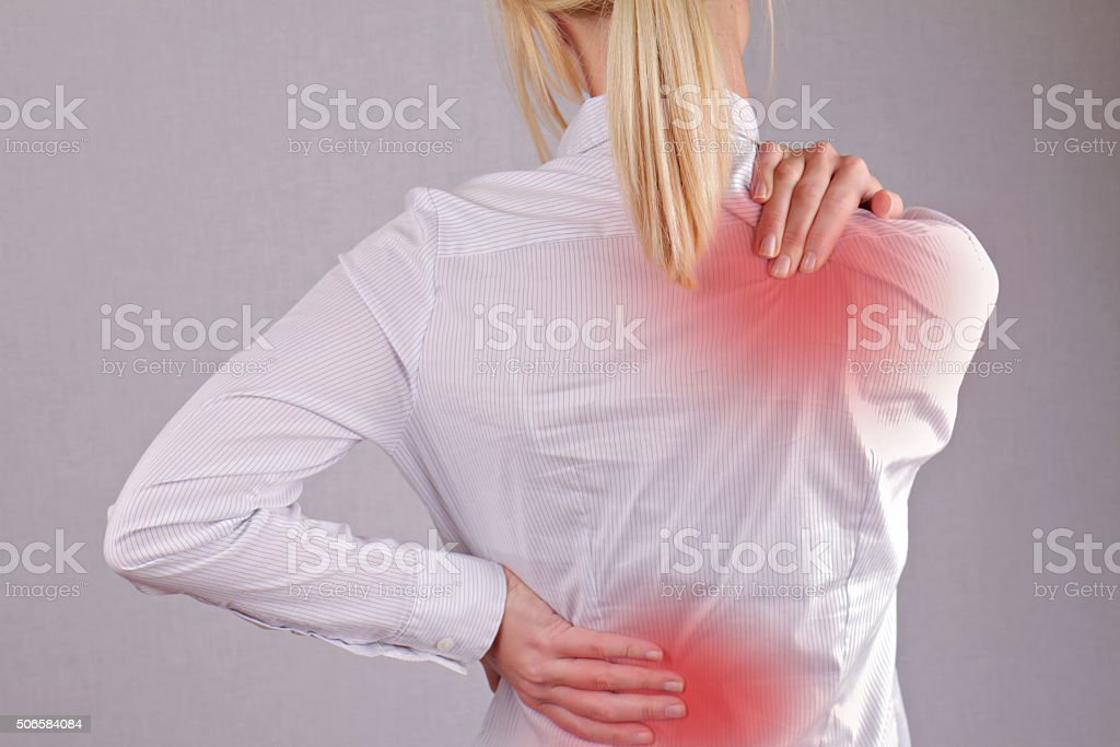 Business woman rubbing her painful back close up. stock photo