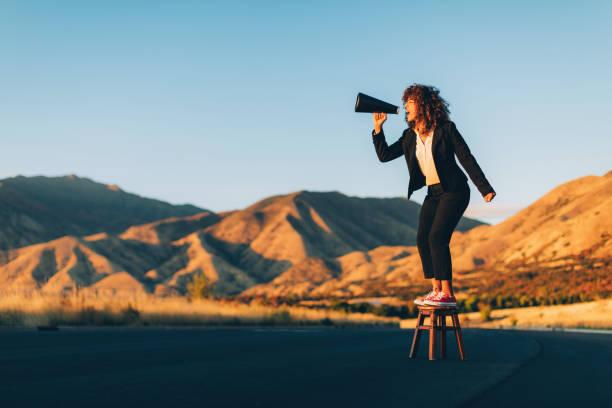Business Woman Shouting Through Megaphone stock photo