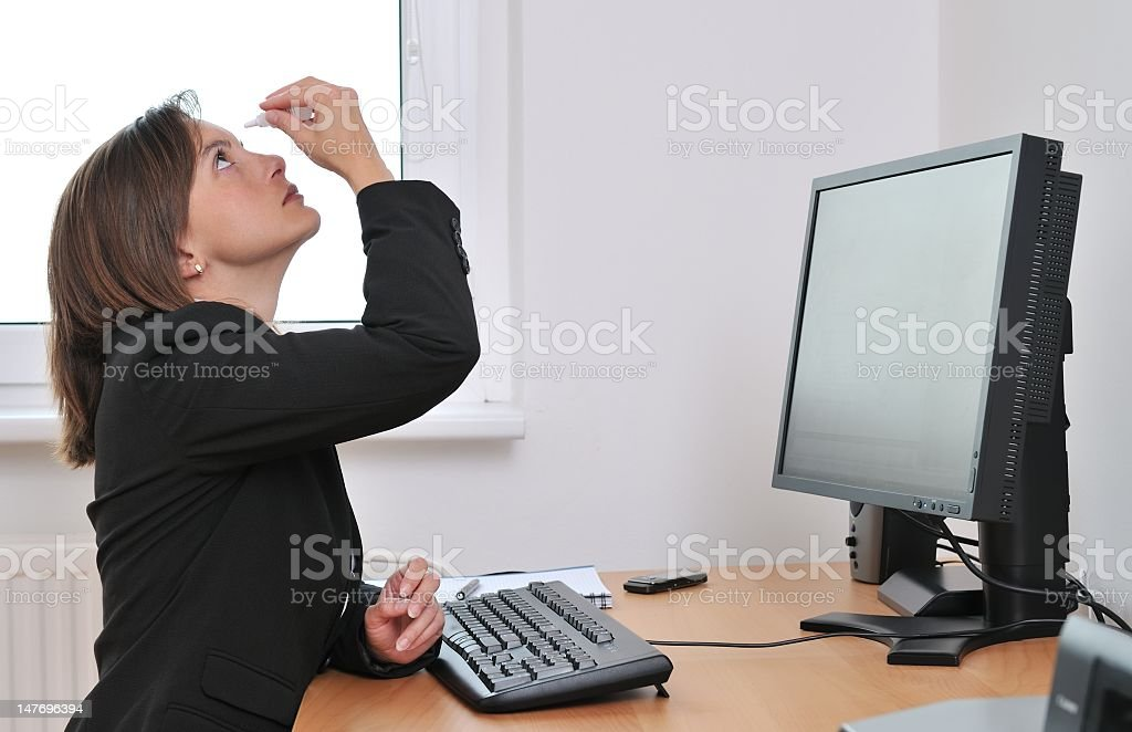 A business woman, sitting at a computer applying eye drops  stock photo