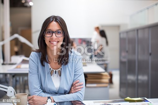 istock Business woman sitting at her desk in corporate office. 619379020