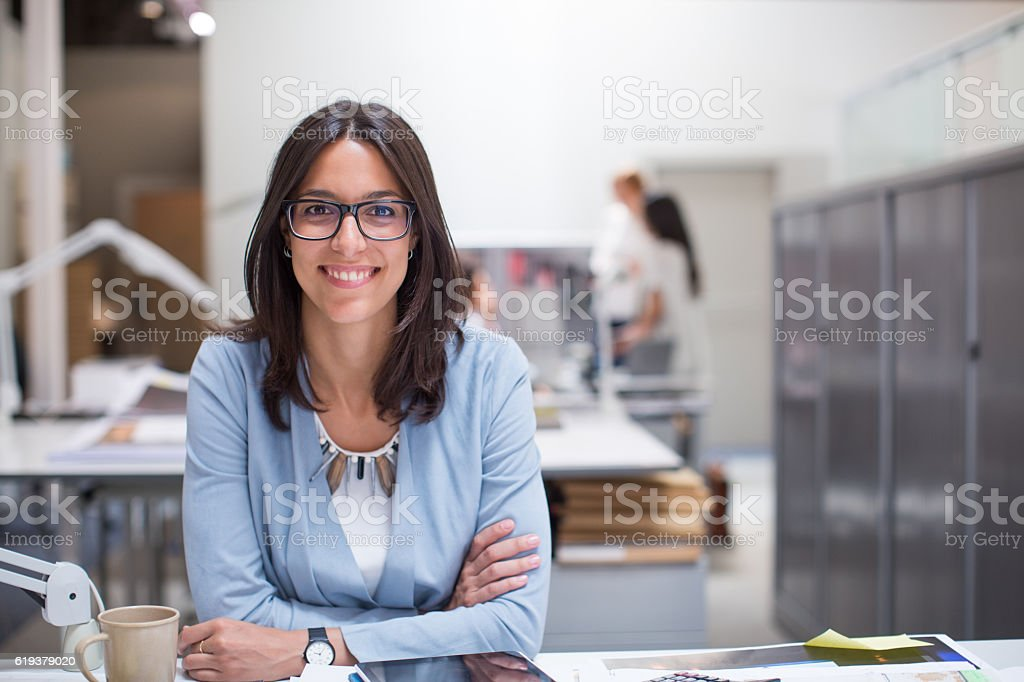 Business woman sitting at her desk in corporate office. stock photo