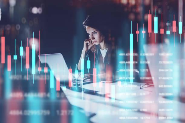Business Frau sitzt im Nachtbüro vor dem Laptop mit Finanzgrafiken und Statistiken auf Monitor. Rote und grüne Kerzenständer und Aktienhandel auf dem Hintergrund. Doppelte Belichtung. – Foto