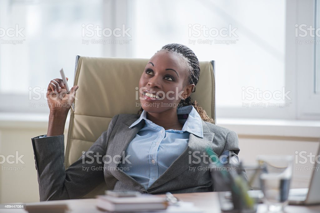Business woman sitting in armchair at office and planning stock photo