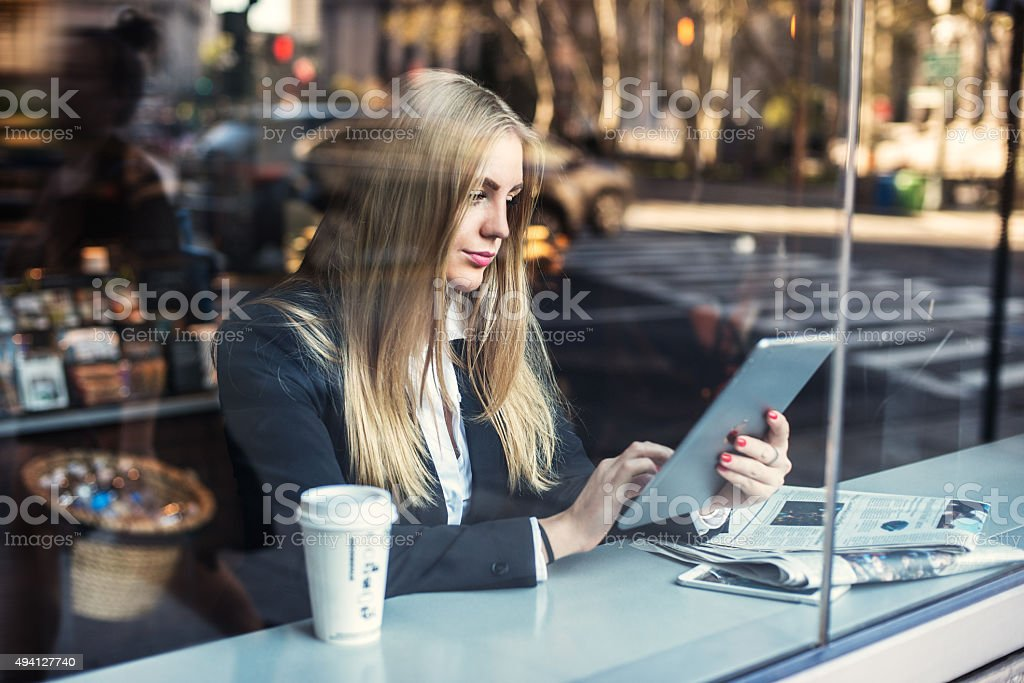 Business woman sitting in cafe and using tablet pc stock photo