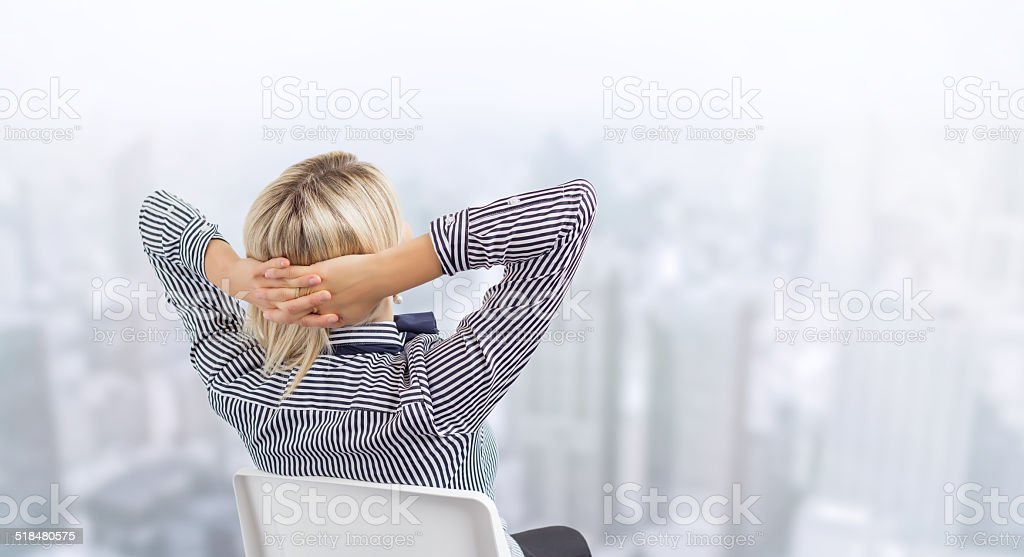 Business woman sitting in chair with city's skyline in background stock photo