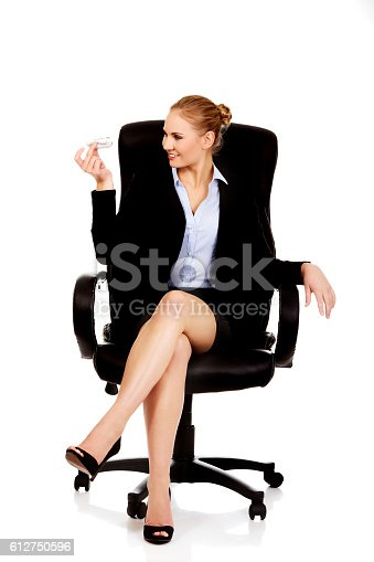 Business woman sitting on wheel chair and holding toy plane.