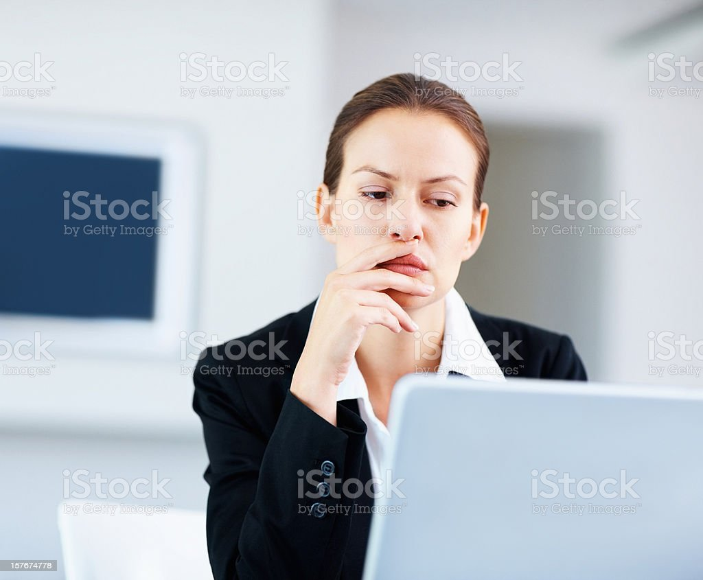 Business woman sitting thoughtfully in front of a laptop royalty-free stock photo