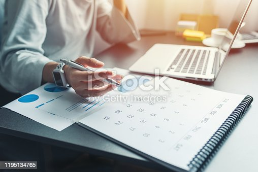 Business woman sitting working and thinking to planner event with calendar and laptop, computer on table at office or home or internet cafe.