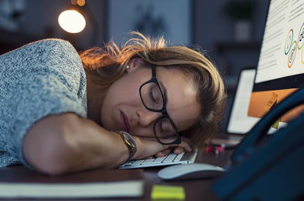 femme d'affaires dormir la nuit sur ordinateur - crouler sous le travail photos et images de collection