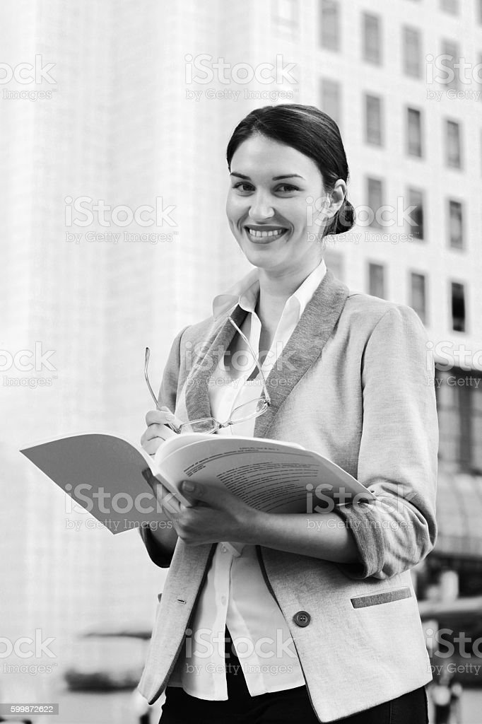 Business woman smiling, in front of building with papers BnW - Photo