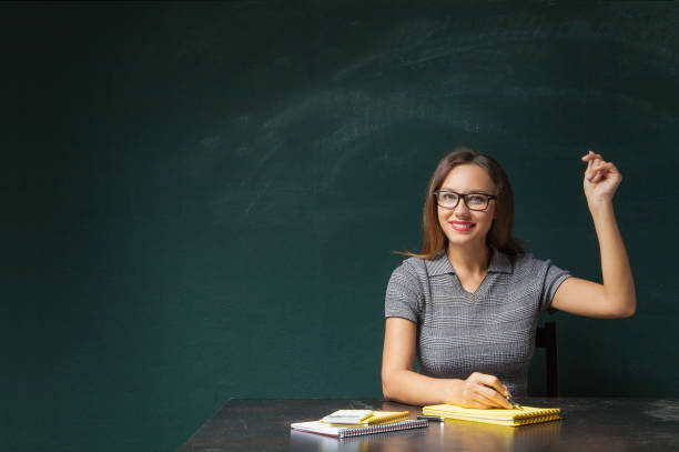Business woman snapping fingers Portrait of young woman snapping fingers on blackboard snapping stock pictures, royalty-free photos & images