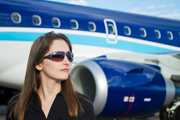 Business woman stading next to an airplane stock photo