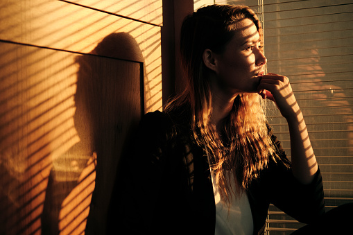 Portrait Of Pensive Business Woman Standing By Window With Venetian Blinds Projecting Shadows At Sunset
