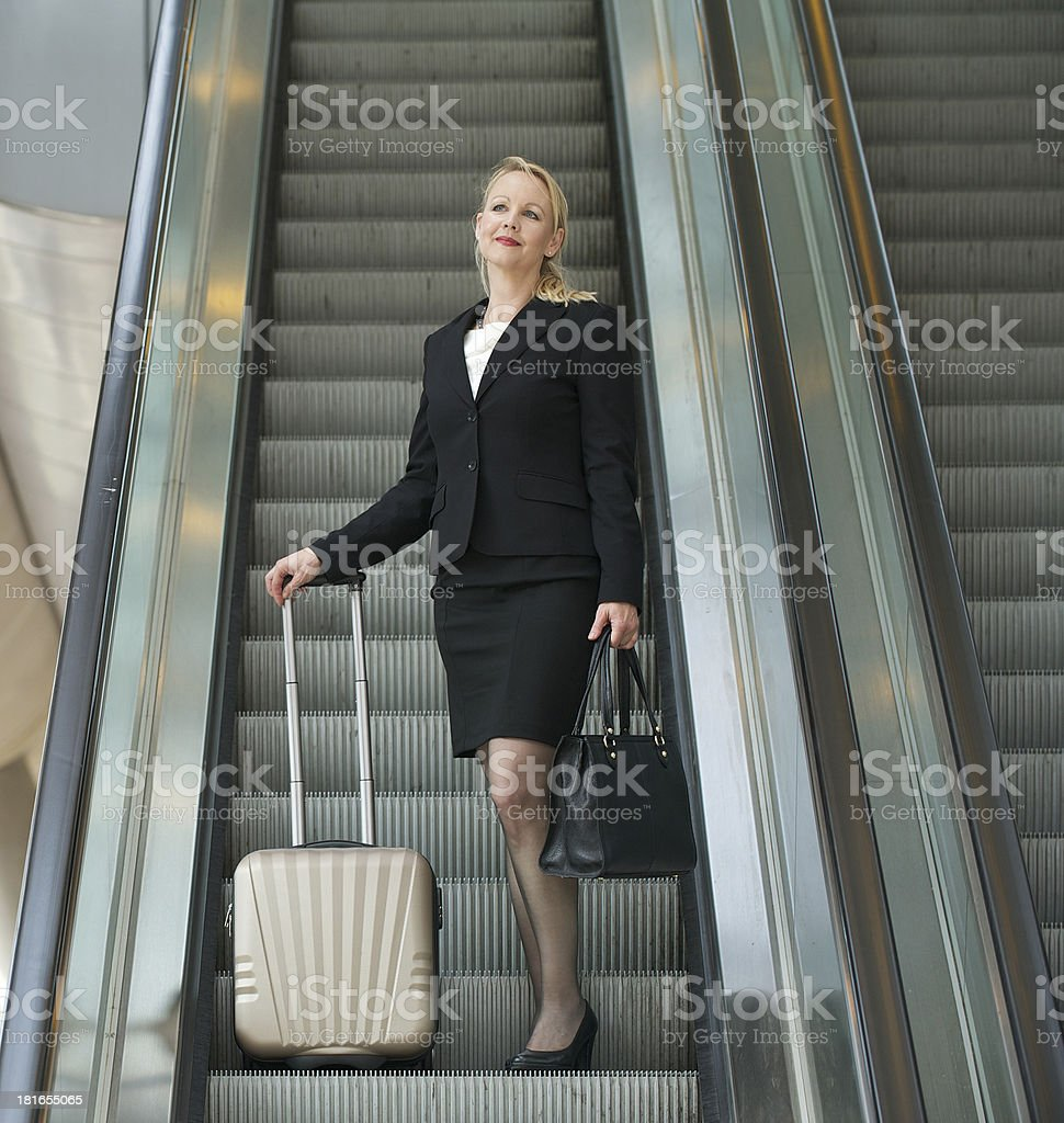 Business woman standing on escalator with travel bags royalty-free stock photo